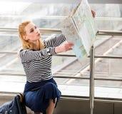 终端镶边的女衬衫的旅游白肤金发的妇女坐在驻地或和看地图 库存图片