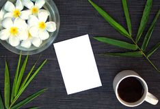 竹叶子和赤素馨花在土气木背景开花 空插件和花卉装饰顶视图 免版税库存照片
