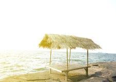 竹在石头的小屋茅屋顶与白色背景的海 免版税库存照片