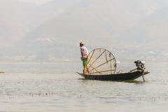 竹小船传染性的鱼的未认出的缅甸渔夫用与手工制造网的传统方式 免版税库存图片