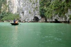 竹小船的游人游览在ha长海湾附近海岛和洞的  免版税库存照片