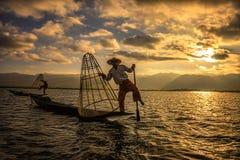 竹小船的缅甸渔夫在日出 库存图片