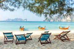竹海滩睡椅和传统长尾巴小船 免版税库存照片