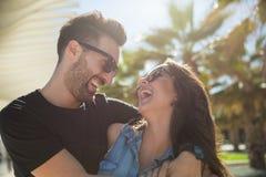 笑一起站立的愉快的夫妇外面 免版税库存图片