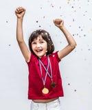 笑与冠军奖牌的成功的漂亮的孩子,庆祝在五彩纸屑 免版税库存图片