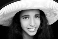 笑与太阳帽子的一个年轻非裔美国人的女孩的画象 免版税库存图片