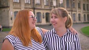 笑与她稀薄的女朋友的壮健白种人女孩,当拥抱外面与微笑时 股票视频