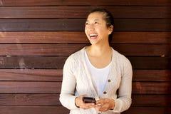 笑与手机的可爱的妇女对木墙壁 图库摄影
