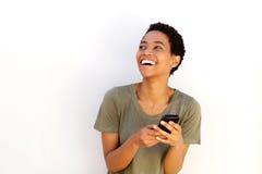 笑与手机的美丽的年轻黑人妇女 免版税库存照片