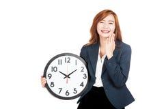 笑与时钟的愉快的亚裔女实业家 图库摄影