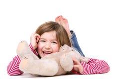 笑与玩具熊的女孩 免版税库存图片