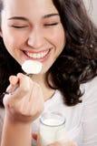 笑与眼睛的愉快的妇女闭上,当吃酸奶时 免版税库存照片