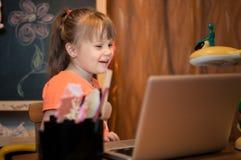 笑与膝上型计算机的女孩 免版税库存图片