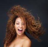 笑与头发吹的乐趣和愉快的少妇的画象 免版税库存图片