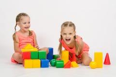 笑两个的女孩无法控制地演奏模子 免版税库存图片