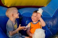 笑两个的男孩,他们分享棉花糖 库存照片