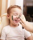 笑作为母亲的小男孩绘他的面孔 图库摄影