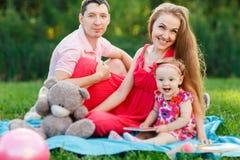 笑做父母与女儿坐格子花呢披肩在公园 免版税库存图片