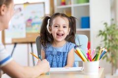 笑儿童的小女孩,在她的绘的五颜六色的铅笔playtable 免版税库存图片