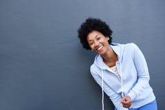 笑反对灰色背景的快乐的年轻非洲妇女 免版税库存图片