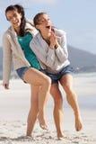 笑和享用海滩的两名无忧无虑的妇女 图库摄影