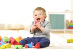 笑和使用与在地毯的玩具的婴孩 库存照片