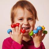 笑和使用与色的玩具的逗人喜爱的小女孩 免版税库存图片