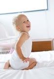 笑和使用在床上的女婴 库存照片