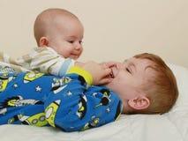 笑和使用在床上的孩子 免版税图库摄影
