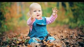 笑和使用在森林的秋天的愉快的女婴 股票录像