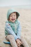 笑和使用在海滩的美丽的女孩  库存图片