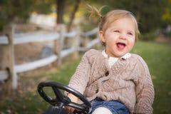 笑和使用在玩具拖拉机的年轻小孩外面 库存图片