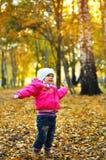 笑和使用在秋天的女婴 免版税库存照片