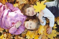 笑和使用在自然步行的秋天的男小学生和小女孩户外 图库摄影