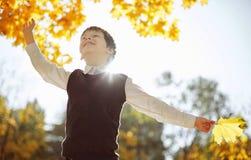 笑和使用在自然步行的秋天的男小学生户外 免版税库存照片