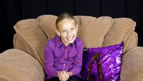 笑和做在舒适椅子的愉快的十几岁的女孩面孔朝向照相机 股票录像