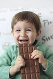 笑和吃巧克力片剂的愉快的婴孩 图库摄影