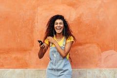 笑和听到与耳机的音乐的年轻黑人妇女户外 便服的阿拉伯女孩有卷曲发型的 库存图片