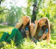 笑和吹肥皂泡的青少年的女孩 免版税库存图片