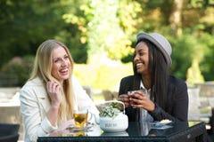 笑和喝茶的多文化朋友 库存图片