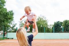 笑和培养她的有网球的俏丽的妈咪女婴在背景中 免版税库存照片