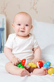 笑和微笑与一个玩具的逗人喜爱的微笑的婴孩在他的手上 L 免版税库存图片