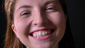 笑和微笑对照相机的年轻迷人的妇女接近的画象,隔绝在黑背景 股票视频