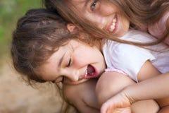 笑和拥抱在夏天公园的两个愉快的小女孩 免版税库存照片