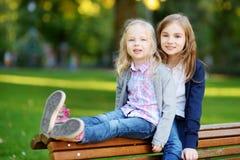 笑和拥抱在夏日的两个可爱的妹在公园 免版税库存照片