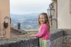 笑和拧紧在城市观点的眼睛的小女孩 库存图片
