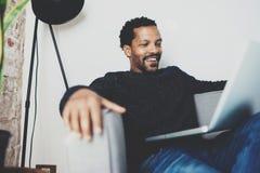 笑和拿着在膝盖的可爱的有胡子的非洲人膝上型计算机,当坐沙发在他的现代家庭办公室时 概念 免版税库存图片