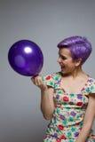 笑和拿着有他的紫罗兰色短发妇女一个气球 免版税库存图片