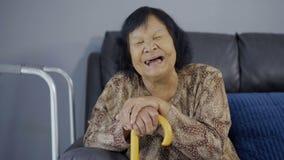 笑和拿着木藤茎的资深妇女在客厅 股票录像