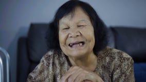 笑和拿着木藤茎的资深妇女的慢镜头 股票录像